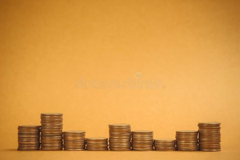 Columnas de las monedas, pilas de monedas en el fondo marrón, negocio a imagenes de archivo