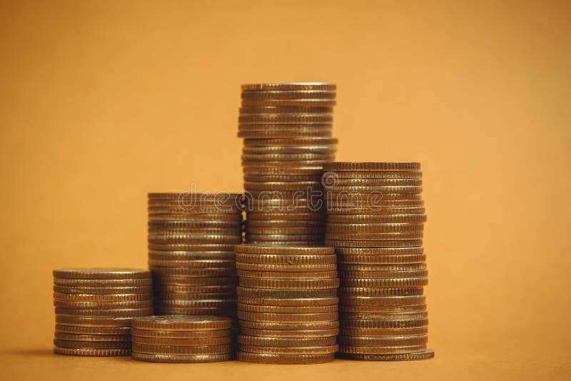 Columnas de las monedas, pilas de monedas en el fondo marrón, negocio a fotos de archivo