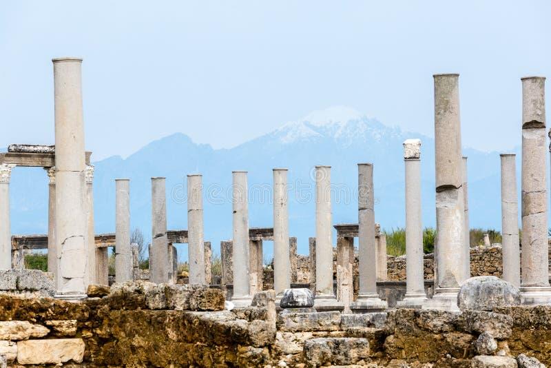 Columnas de mármol en un fondo de montañas en la ciudad antigua de Perge cerca de Antalya, Turquía fotos de archivo