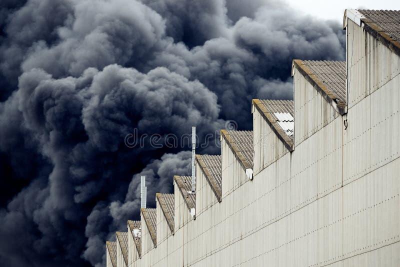 Columnas negras de humo de un fuego industrial tóxico accidental según lo visto de a detrás de un edificio de la fábrica fotografía de archivo libre de regalías