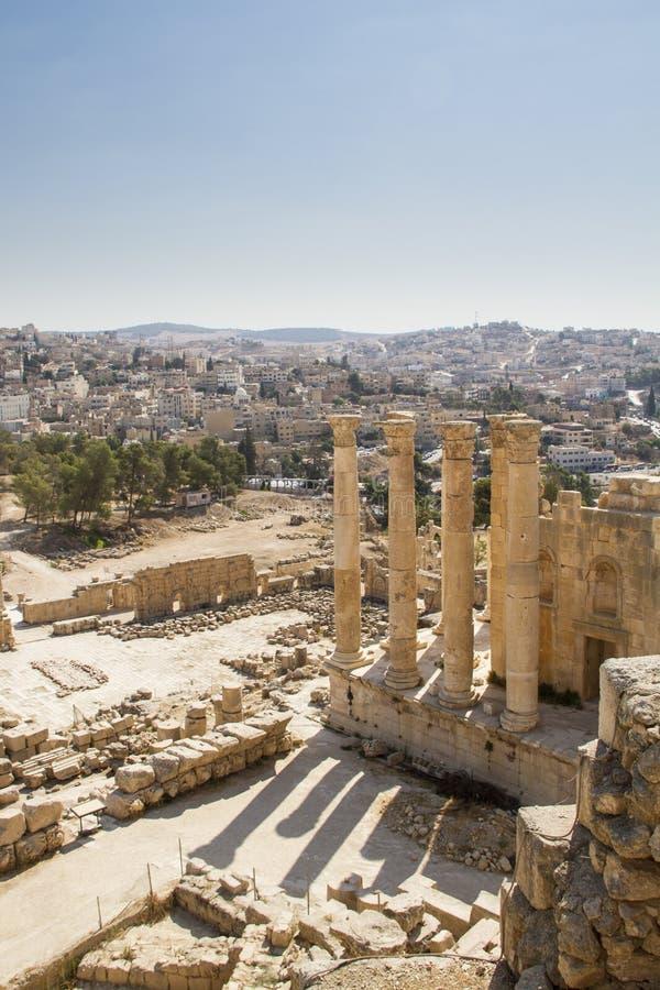 Columnas viejas del jerash con la opinión de la ciudad del jerash imágenes de archivo libres de regalías