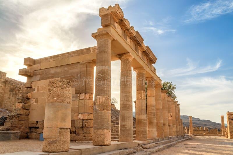 Columnata con el templo principal del pórtico de Lindos Rodas en el fondo de las nubes de la puesta del sol y del sol imágenes de archivo libres de regalías