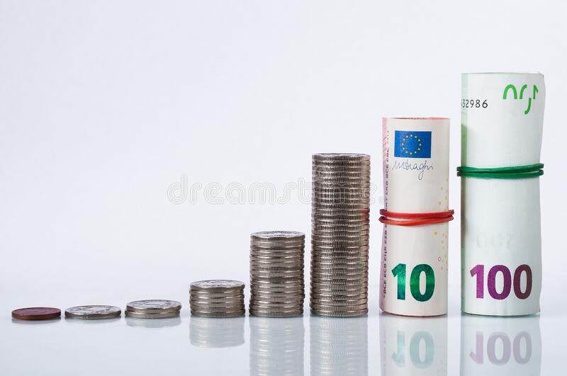 Columns of coins and rolls of euro banknotes. Growth concept on the stock market royalty free stock photography