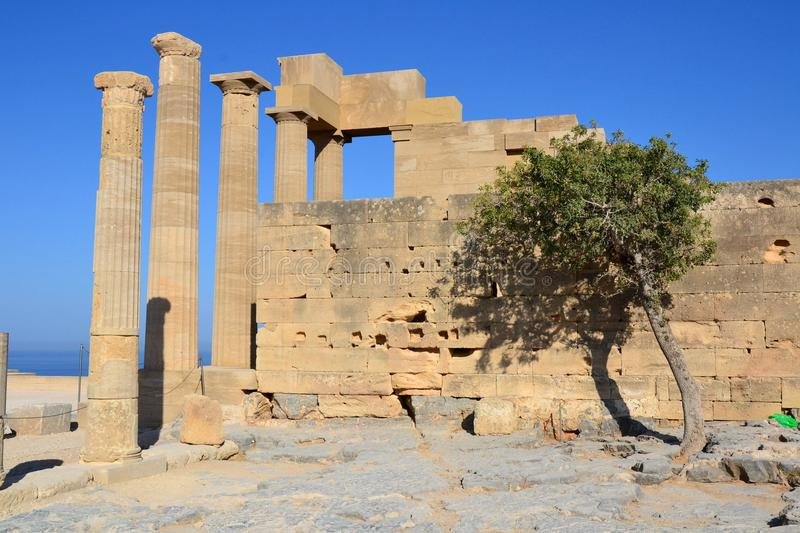 Columns on the hellenistic stoa of the Acropolis of Lindos, Rhodes, Greece, Blue sky, olive tree and beatiful sea view in the back. Ground stock photo