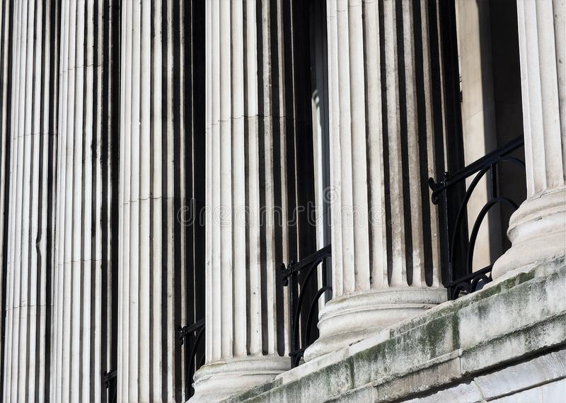 Columns standing tall next to each other. Rows of tall columns stand tall next to each other outside St. Pauls Cathedral. Columns represent strength, uniformity stock image