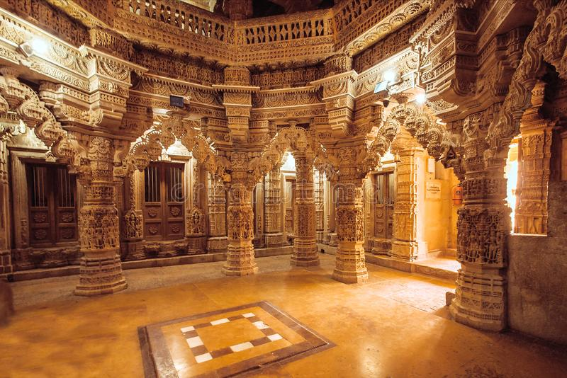 Columns with stone reliefs in Indian temple wall. Ancient architecture example with Jain motifs, Jaisalmer of India. Columns with stone reliefs in Indian temple stock image