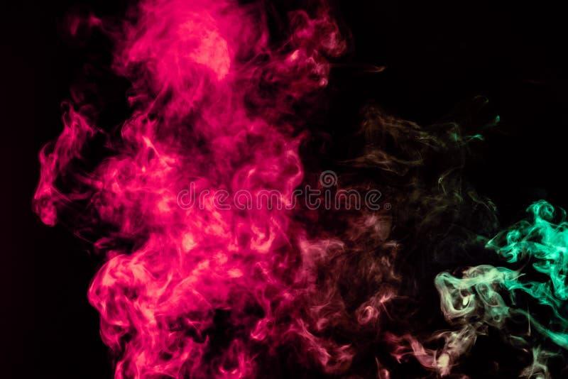 Coluna de fumo bonita na luz brilhante de n?on de vermelho, de verde, o rosa e a turquesa em um fundo preto expirado fora do vape foto de stock royalty free