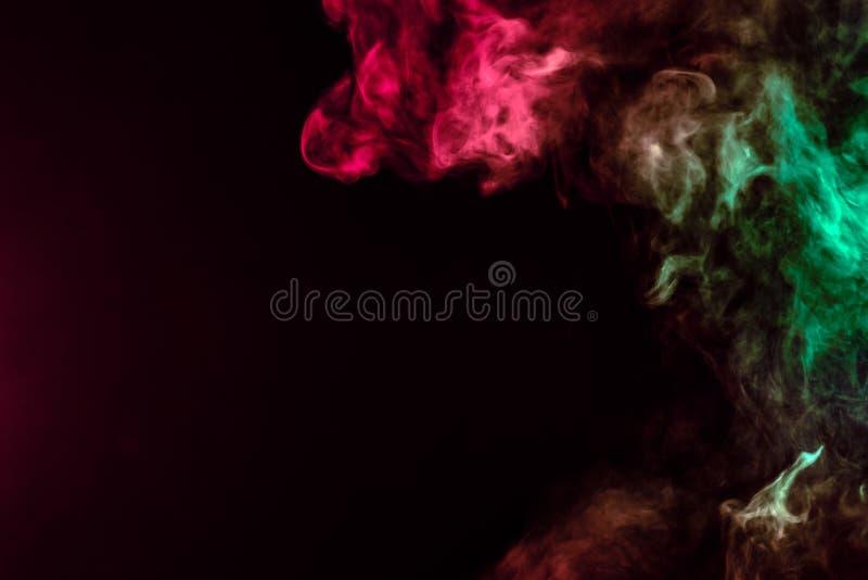 Coluna de fumo bonita na luz brilhante de n?on de vermelho, de verde, o rosa e a turquesa em um fundo preto expirado fora do vape fotografia de stock