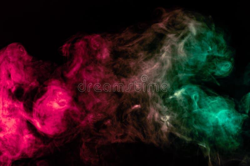 Coluna de fumo bonita na luz brilhante de n?on de vermelho, de verde, o rosa e a turquesa em um fundo preto expirado fora do vape fotografia de stock royalty free