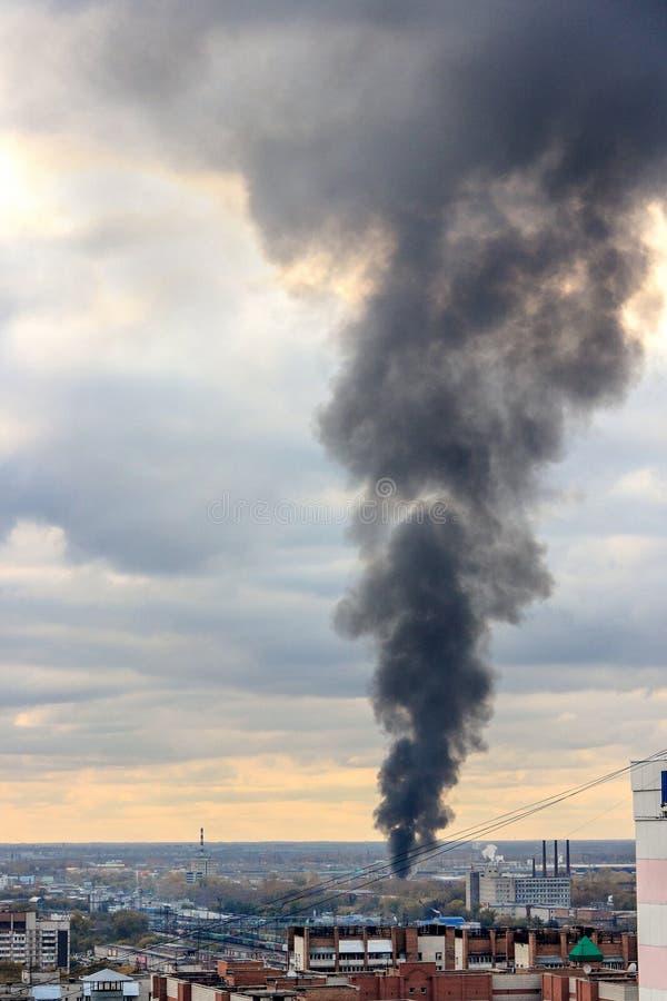 A coluna de fumo preta devido ao fogo aumenta ao céu fotos de stock