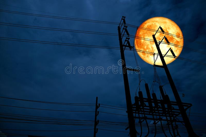coluna elétrica do poder da silhueta da parte traseira da lua do sangue na noite escura s fotos de stock