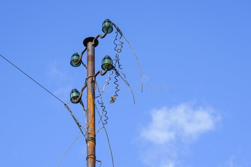 Coluna elétrica velha com isoladores de vidro e fios desligado fotografia de stock