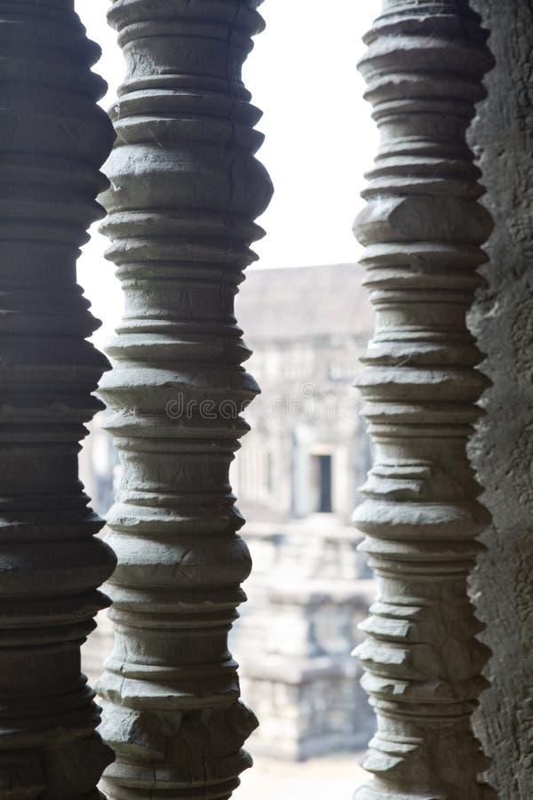 Colunas cinzeladas, trilho-cargos, em aberturas da janela em Angkor Wat Temple, Siem Reap, Camboja São executados manualmente mui imagem de stock