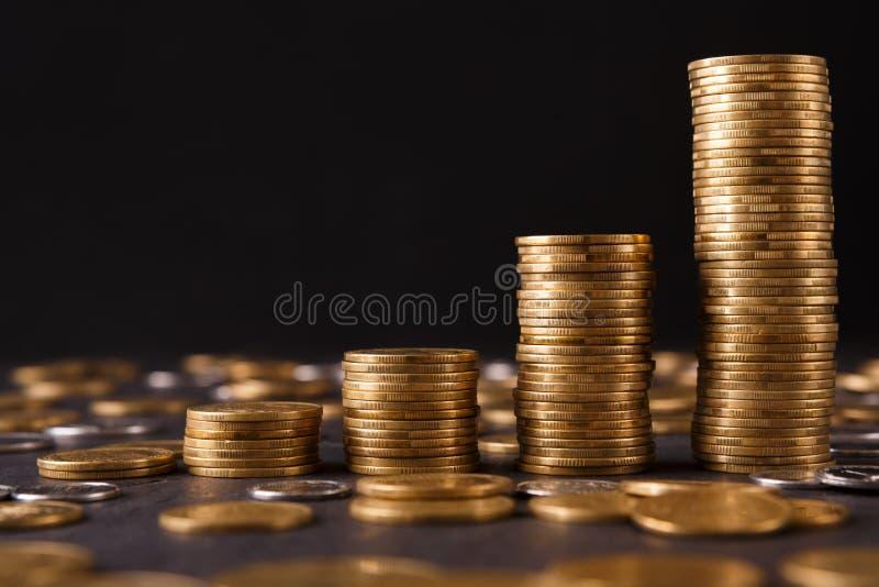 Colunas crescentes de moedas de ouro na tabela imagens de stock