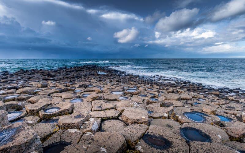 Colunas da rocha vulcânica da calçada de Giants sob o céu tormentoso, Irlanda do Norte fotografia de stock