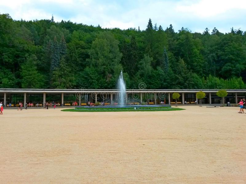 Colunata de termas, de fonte, de povos, de árvores e de floresta de Luhacovice no fundo imagem de stock royalty free