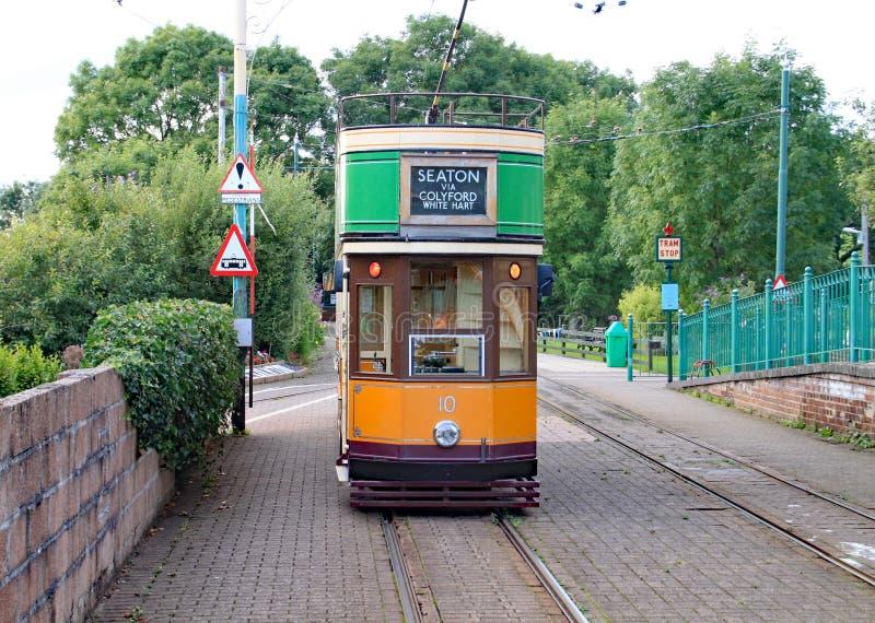 COLYTON, DEVON, ANGLETERRE - 6 AOÛT 2012 : Un tram orange et vert repose vide dans la station de Colyford sur la tramway de Seato photographie stock