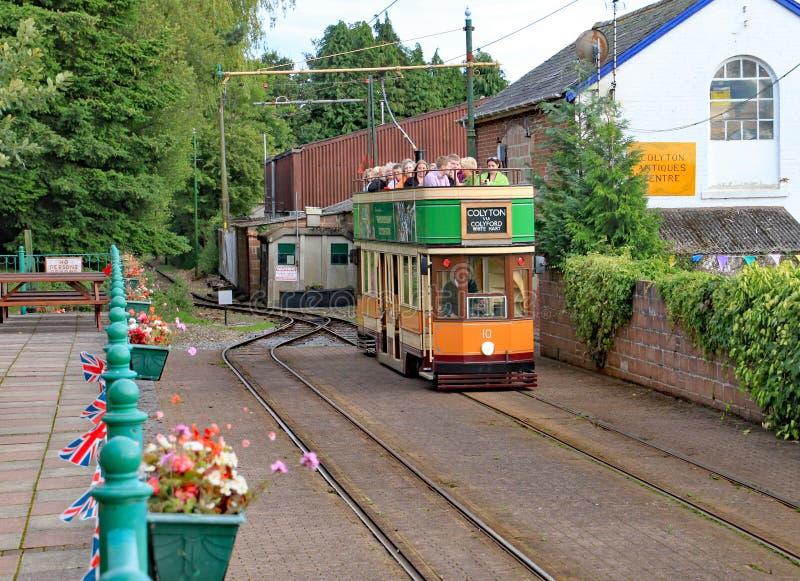 COLYTON, DEVON, ENGELAND - AUGUSTUS ZESDE 2012: Een oranje en groene tram trekt in Colyford-post op het Seaton-tramspoor passagie stock foto