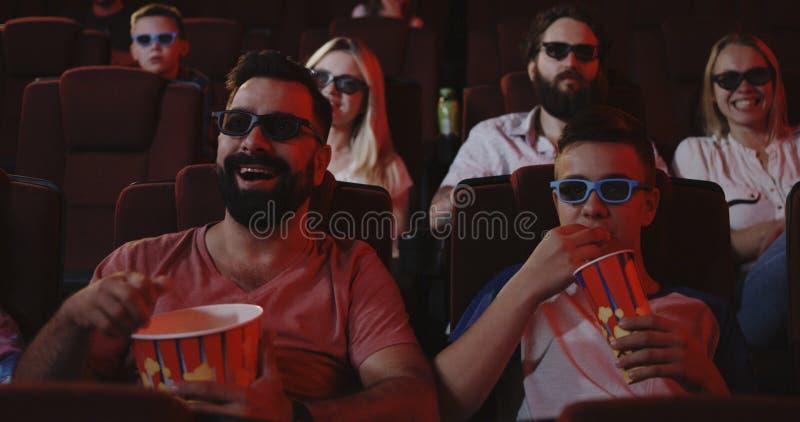 Comédia de observação do pai e do filho no cinema fotografia de stock
