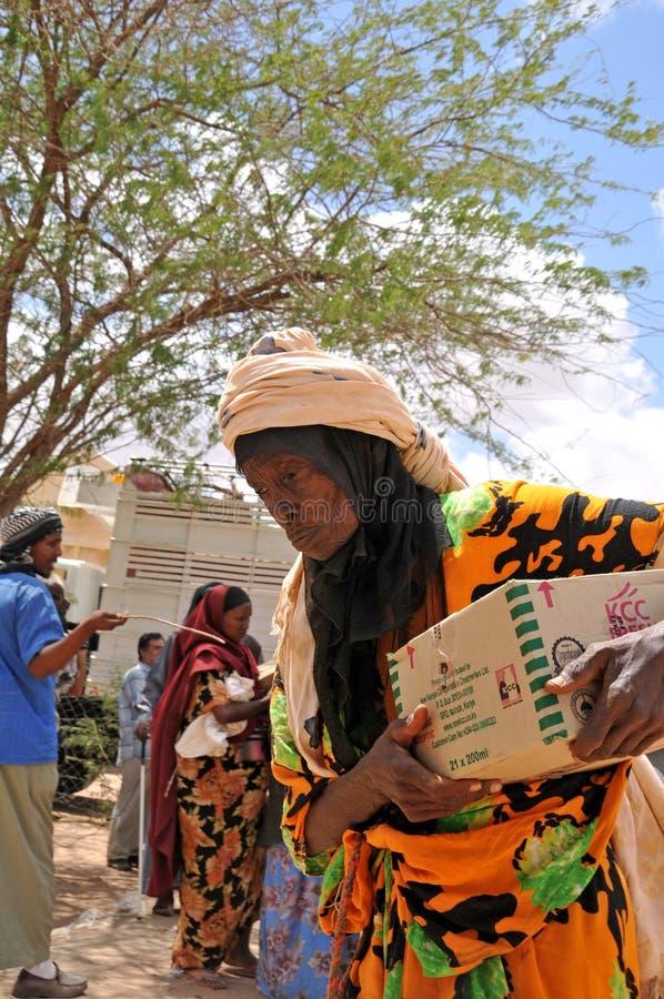 Com auxílio os africanos após a mulher adulta retornam em casa fotografia de stock