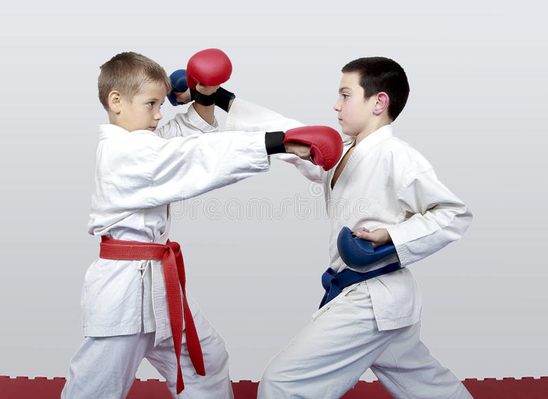 Com a correia azul e vermelha os meninos treinam o karaté emparelhado dos exercícios imagem de stock royalty free