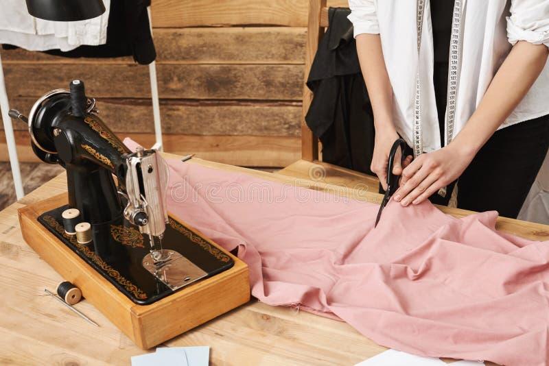 Com esforço acontecerá Tiro colhido da tela fêmea do corte do alfaiate ao trabalhar na linha nova do vestuário para sua loja imagens de stock