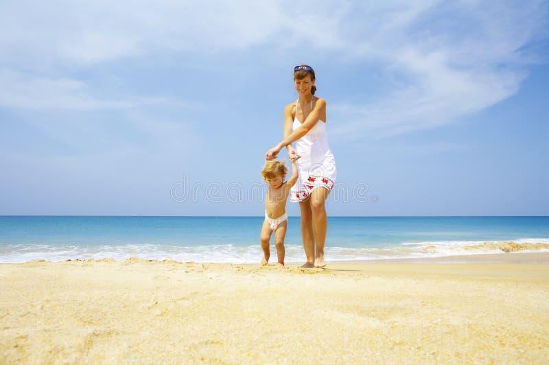 Com o bebê na praia foto de stock