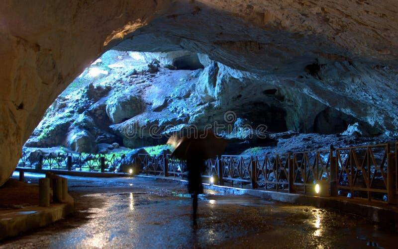 Com o guarda-chuva na caverna foto de stock