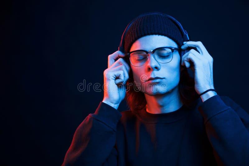 Com os olhos fechados Estúdio fotografado em estúdio escuro com luz neon Retrato de homem sério fotografia de stock royalty free