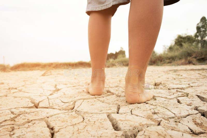 Com os pés descalços na terra com terra seca e rachada Afetado do aquecimento global fez alterações climáticas imagens de stock