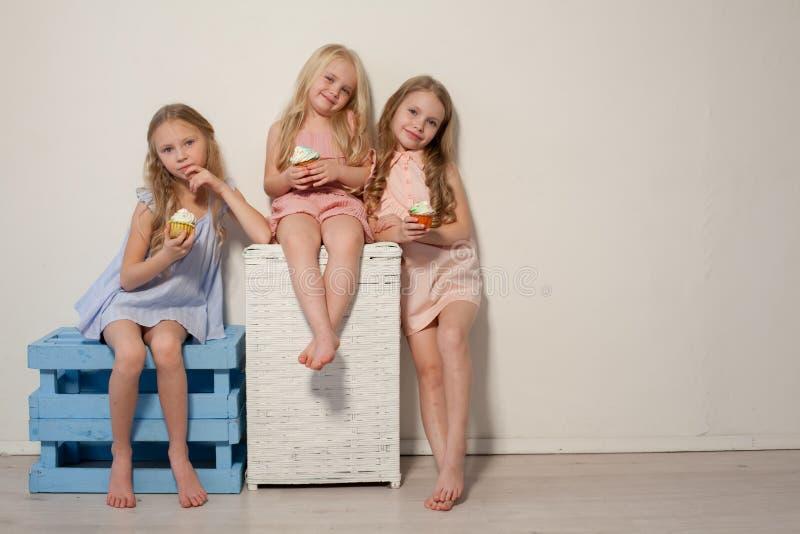 Coma as meninas doces do pirulito três dos doces louras imagem de stock