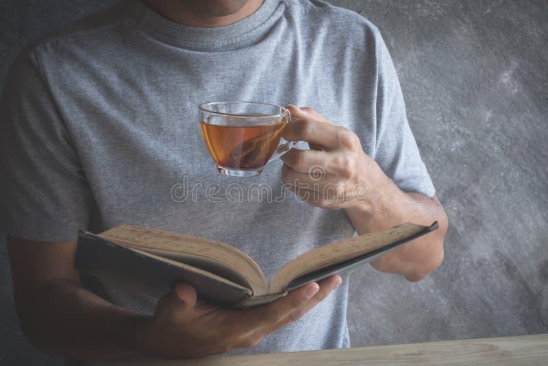 Coma el té caliente que lee la tabla de madera foto de archivo libre de regalías
