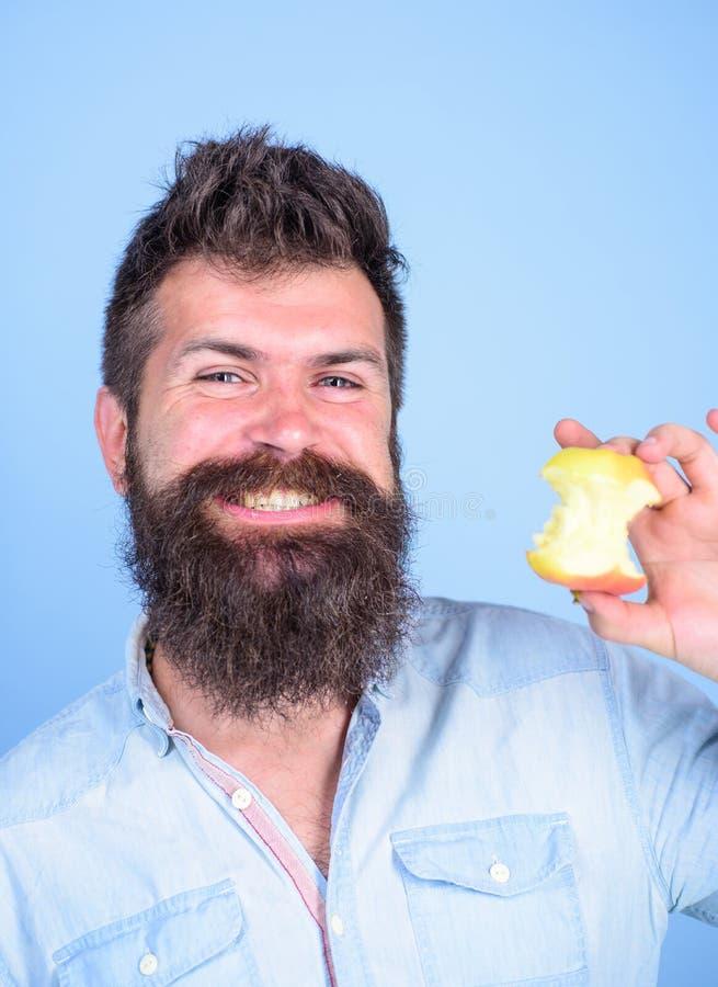 Coma la manzana cada día Barba larga del inconformista hermoso del hombre que come la manzana Tocón casi comido hambriento de la  fotos de archivo libres de regalías