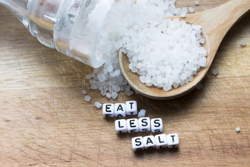Coma menos mensaje de la sal escrito cerca de la cuchara de madera por completo de la sal y de la coctelera granuladas en fondo r fotos de archivo libres de regalías