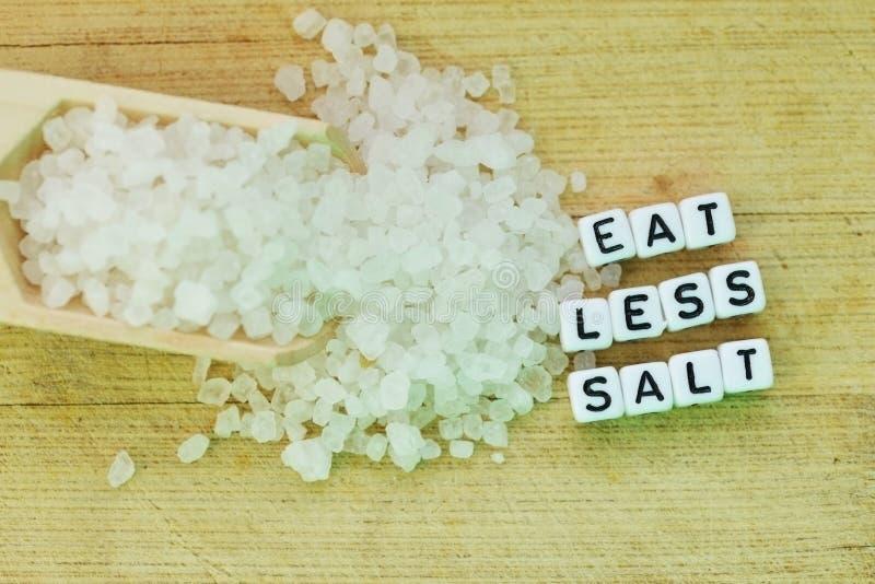 Coma menos recomendaci?n de la sal con las letras pl?sticas y la sal granulada en la tajadera de madera imagenes de archivo