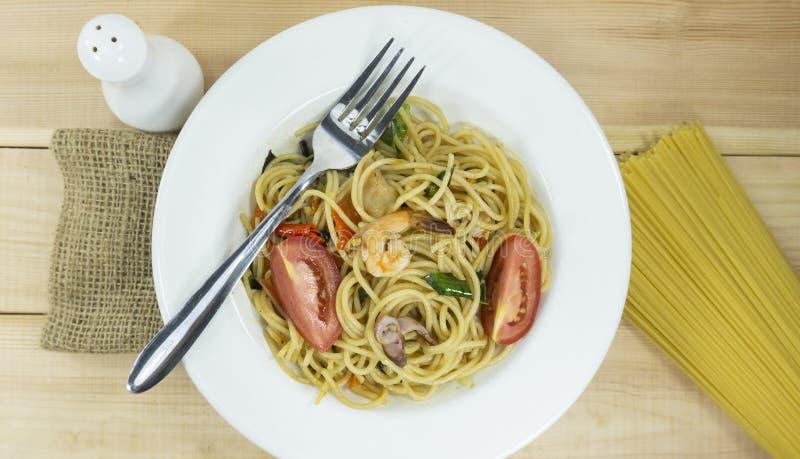 Coma os espaguetes do almoço em uma forquilha branca da decoração dos suportes do prato e linhas cruas dos espaguetes no fundo de fotografia de stock