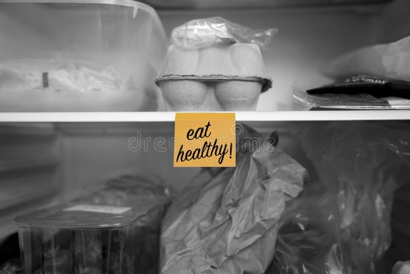 Coma sano escrito en una nota de post-it pegada en un estante del refrigerador con la comida fotografía de archivo libre de regalías