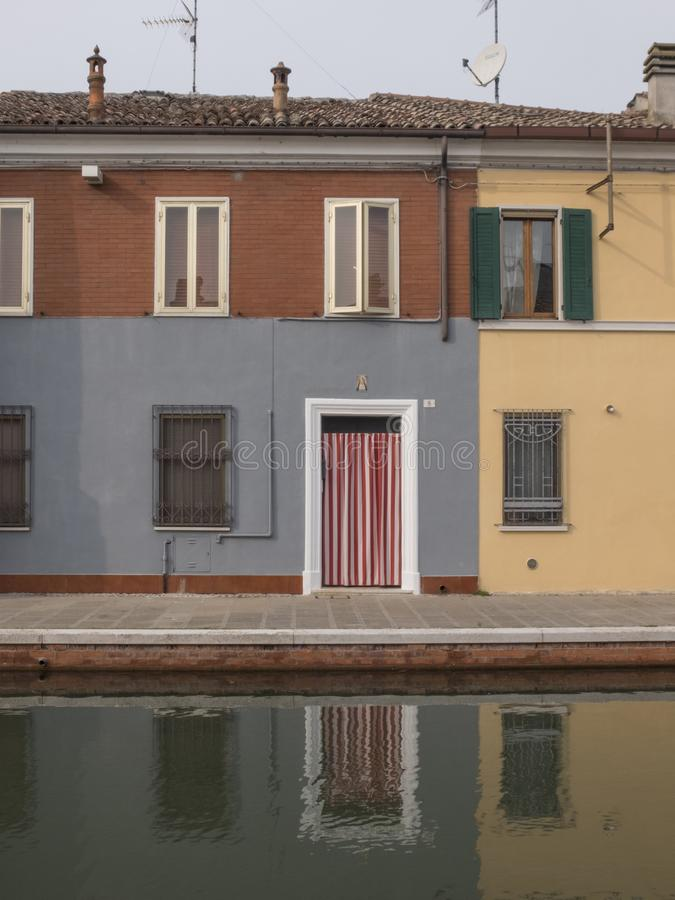 Comacchio, FE, Italy - November 4, 2017: exterior facing room overlooking the canal of Comacchio. Reflection in the water. White stock image