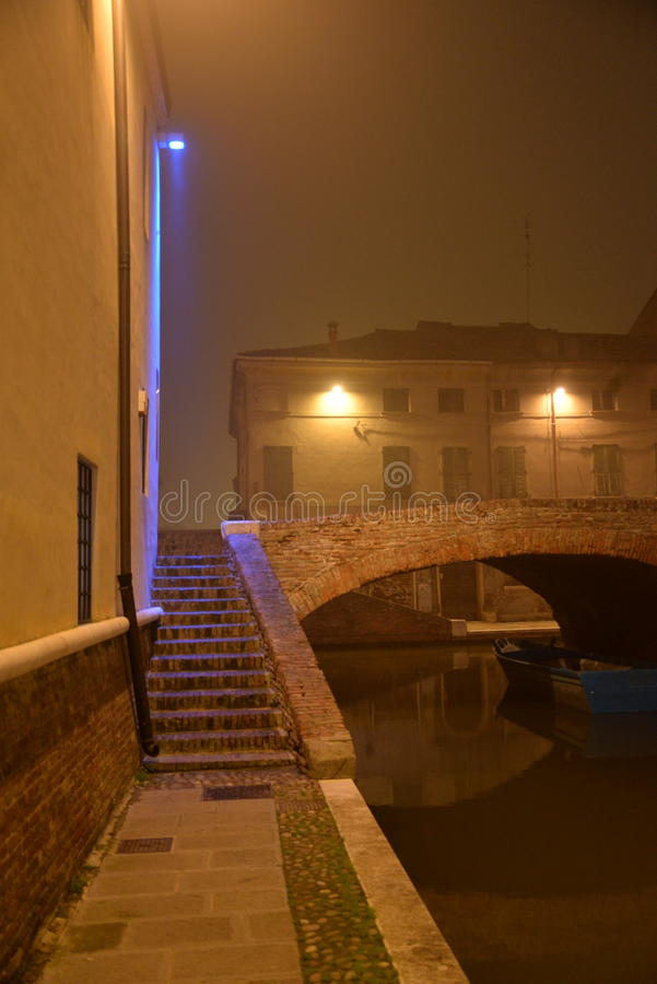 Comacchio, Italy. Night view of a canal bridge. winter fog royalty free stock image