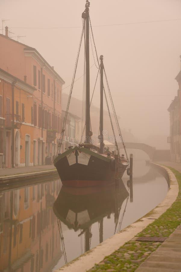 Comacchio, kanalbro och gammalt skepp i vinter Ferrara Emilia Romagna, Italien arkivbilder