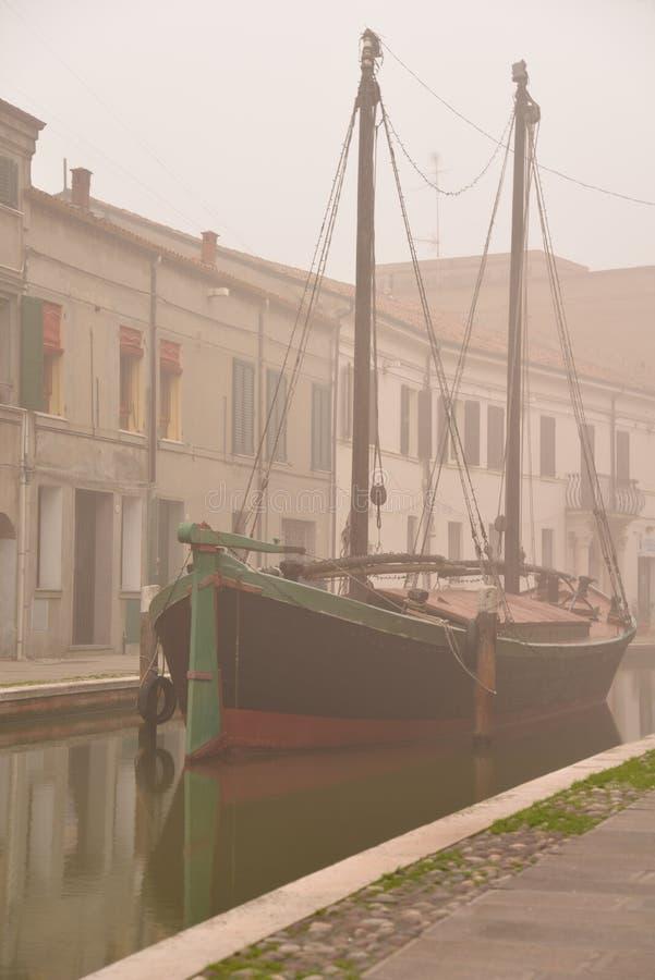 Comacchio, kanalbro och gammalt skepp i vinter Ferrara Emilia Romagna, Italien arkivfoto
