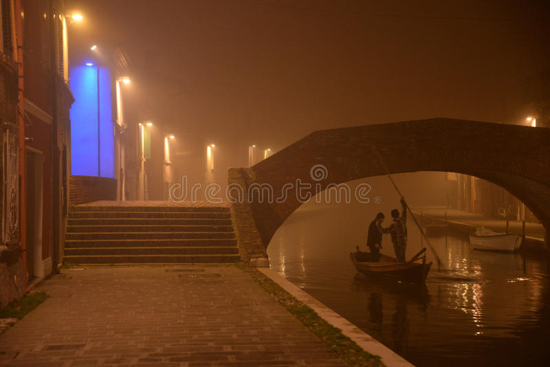 Comacchio, night view of a canal bridge, people on a boat. winter fog royalty free stock photography