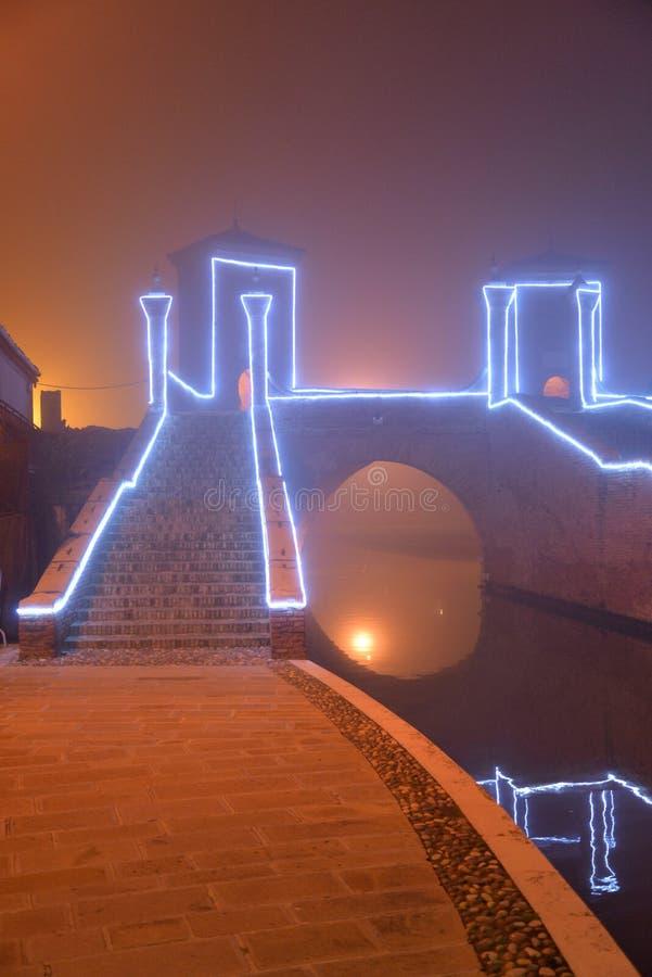 Comacchio upplyst kanalbro i vinter Ferrara Emilia Romagna, Italien royaltyfria foton