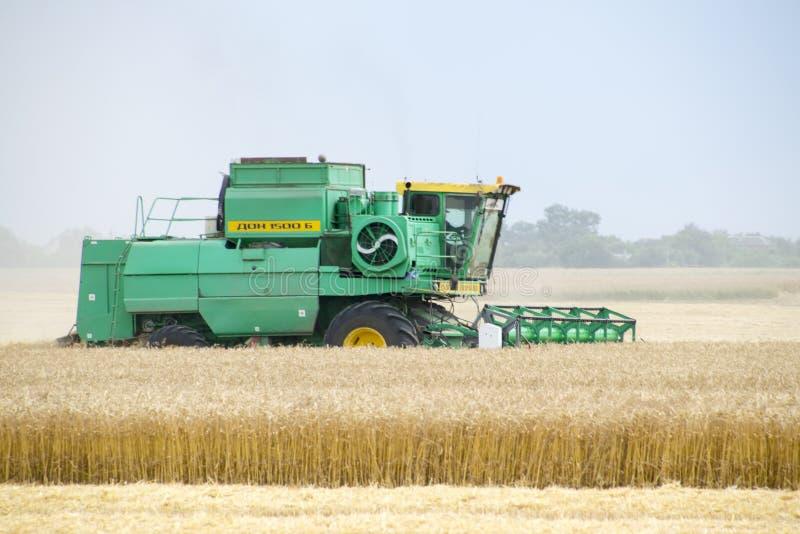 Combain samlar på veteskörden Jordbruks- maskineri i fältet arkivbilder