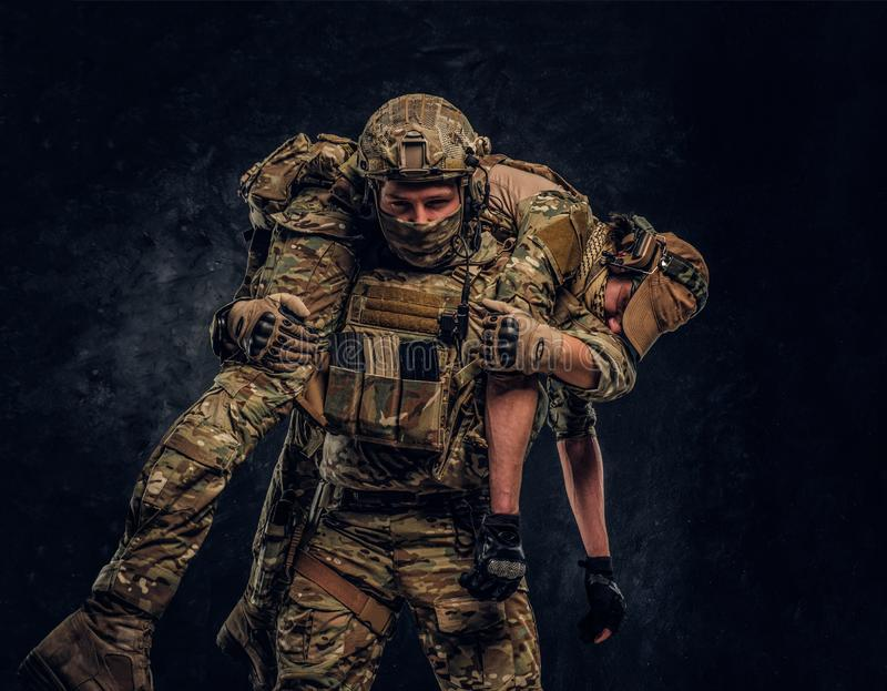 Combat conflict, special mission, retreat. Soldier special forces rescue his wounded teammate carrying him on his. Shoulders from the battlefield. Studio photo royalty free stock photography