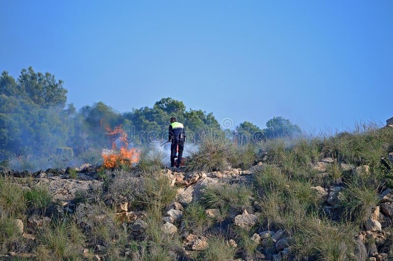 Combat d'un feu de Bush avec un extincteur photos libres de droits