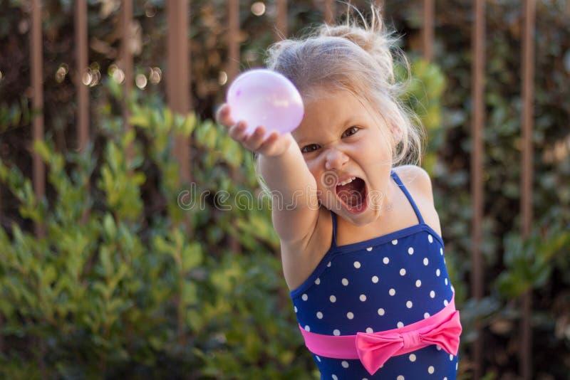 Combat de ballon d'eau de petite fille image stock