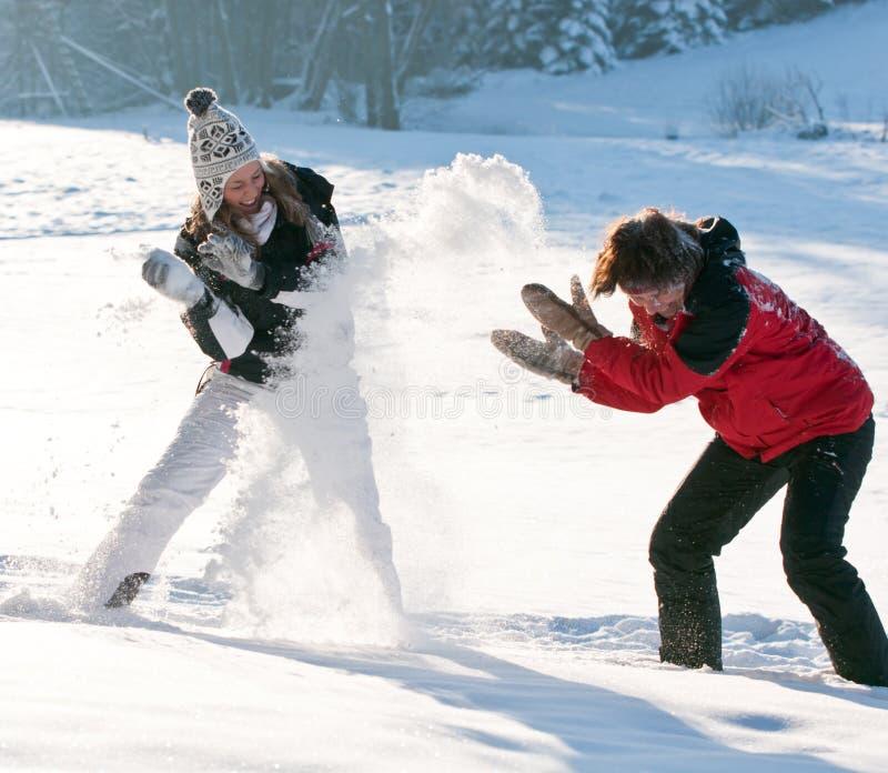Combat de boule de neige et amusement de l'hiver photographie stock