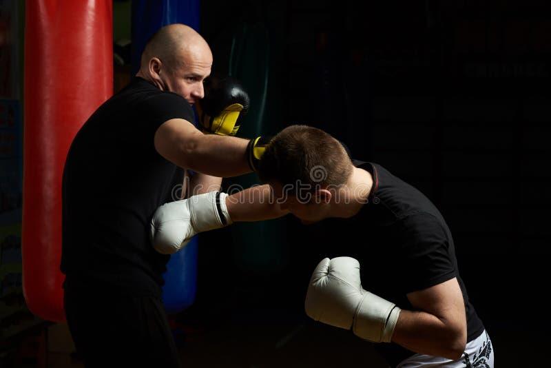 Combat de boxe entre le jeune homme deux photographie stock libre de droits