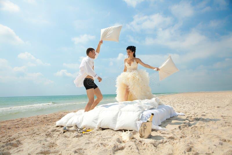 Combat de couples de nouveaux mariés avec des oreillers images libres de droits